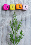 Dill with letter cube concept against gray wood Stock Photo