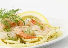 Dill Sprigs Garnish Shrimp Scampi On Pasta. Dill Sprigs and lemon slice provide garnishes for shrimp scampi served over spaghetti pasta on white serving plate Stock Photos