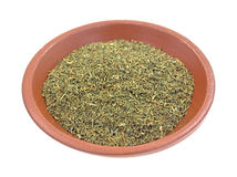 Dill weed in a small bowl. A small clay bowl with a portion of dried dill weed on a white background royalty free stock images