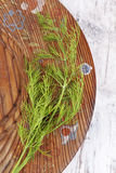 Dill on wooden plate. Stock Images