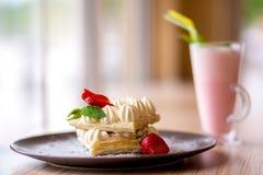 Dillanden med den kräm- jordgubben och mjölkar coctailen Arkivbild