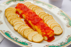 Dilua as fatias brindadas crocantes do baguette empilhadas acima na placa branca com salsa vermelha e o queijo que encontram-se n Foto de Stock Royalty Free