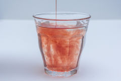 Diluted fruit juice poured into glass of water Royalty Free Stock Photo