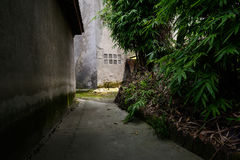 Dim alley behind aged building Royalty Free Stock Images