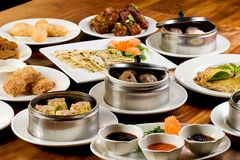 Dim Sum. A table filled with delicious Chinese Dim Sum plates including dumplings, flat bread, cake, meat balls and more Stock Images