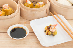 Dim Sum in Bamboo Trays. Dim Sum in white plate on wooden background Royalty Free Stock Photography