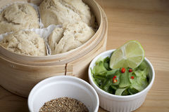 Dim Sum Coconut Buns with Pickled Cucumber, Red Chillie, Lime and Toasted Sesame Seeds. Dim sum coconut buns steamed in a bamboo basket and served with pickled Royalty Free Stock Photography