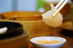 Dim Sum or Har Gow soaked with chili sauce and was picked by chopsticks over a sauce dish. popular appetizer Chinese food royalty free stock photo