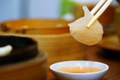 Dim Sum ou Har Gow imbibé de la sauce chili et a été sélectionné par des baguettes au-dessus d'un plat de sauce nourriture popula photo libre de droits