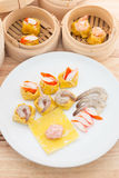 Dim sum shrimp dumpling. Dim Sum in Bamboo Trays on Wooden Background Royalty Free Stock Photo
