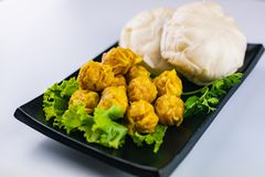 Dim Sum - Steamed dumplings and steamed Chinese pork buns.  royalty free stock image