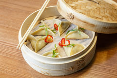 Dim sums with chicken meat in asian restaurant. Dim sums - wontons -with a chicken meat  in a bamboo box on wooden table in asian restaurant Royalty Free Stock Images