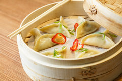 Dim sums with chicken meat in asian restaurant. Dim sums - wontons -with a chicken meat  in a bamboo box on wooden table in asian restaurant Royalty Free Stock Photography