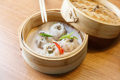 Dim sums with pork and mushrooms in asian restaurant. Dim sums with pork and mushrooms in a bamboo steamer on a wooden table in asian restaurant Stock Photography