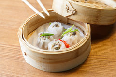Dim sums with pork and mushrooms in asian restaurant. Dim sums with pork and mushrooms in a bamboo steamer on a wooden table in asian restaurant Stock Photo