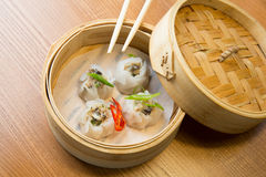 Dim sums with pork and mushrooms in asian restaurant. Dim sums with pork and mushrooms in a bamboo steamer on a wooden table in asian restaurant Royalty Free Stock Photography