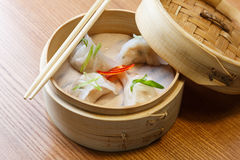 Dim sums with shrimps in asian restaurant. Dim sums with shrimps in a bamboo steamer on a wooden table in asian restaurant Royalty Free Stock Photos
