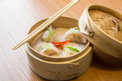 Dim sums with shrimps in asian restaurant. Dim sums with shrimps in a bamboo steamer on a wooden table in asian restaurant Stock Images