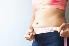 Dimagramento della donna con il grasso della pancia, grasso di misurazione della pancia della donna sportiva fotografia stock libera da diritti