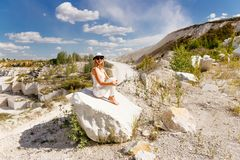Dimagrisca la donna abbronzata che si siede su un pezzo di marmo, le montagne, il cielo, la strada polverosa fotografia stock libera da diritti