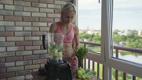 Dimagrisca la donna sportiva che produce un frullato verde casalingo della disintossicazione video d archivio