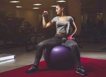 Dimagrisca, ragazza del culturista che solleva le teste di legno pesanti, sieda sulla palla per forma fisica durante l'allenament Fotografia Stock Libera da Diritti