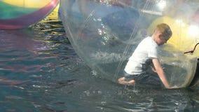 Dimenamenti del ragazzino dentro una grande palla gonfiabile archivi video
