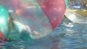 Dimenamenti della bambina dentro la grande palla gonfiabile video d archivio