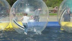 Dimenamenti della bambina dentro la grande palla gonfiabile stock footage