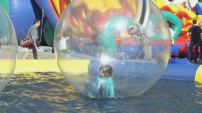 Dimenamenti della bambina dentro la grande palla gonfiabile archivi video
