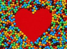 Dimensión de una variable blanca del corazón con el fondo del caramelo Foto de archivo