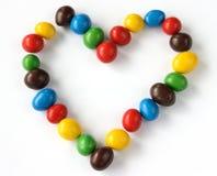 Dimensión de una variable del corazón creada de los pequeños caramelos Imagen de archivo libre de regalías