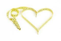 Dimensión de una variable del corazón de la cinta métrica - salud, concepto del peso Foto de archivo