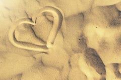 Dimensión de una variable del corazón drenada en la arena Verano y fondo de la playa Imágenes de archivo libres de regalías