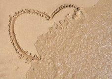 Dimensión de una variable del corazón en la arena de la playa Fotografía de archivo libre de regalías