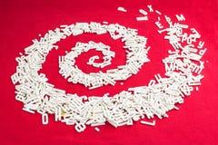 Dimensionale brieven verspreide spiraal op rode achtergrond Stock Foto
