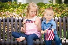 Dimensione di Comparing American Flag del fratello e della grande sorella Immagine Stock Libera da Diritti