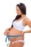 Dimensione di misurazione della giovane donna incinta del nastro di misurazione della pancia Fotografie Stock