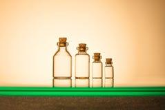 Dimensione quattro delle bottiglie di vetro su fondo giallo immagini stock