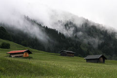 three houses on grass forest breath fog in Gerold village Bavaria Germany Alps Stock Photos