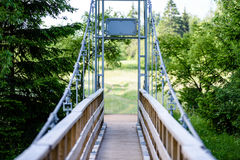 Diminishing perspective of metal suspension footbridge over rive Royalty Free Stock Image