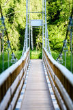 Diminishing perspective of metal suspension footbridge over rive Royalty Free Stock Photos