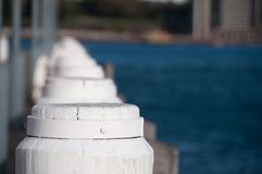 Diminishing perspective view of white wooden poles. And blue water royalty free stock photos