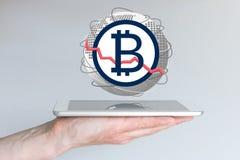 Diminuição do conceito global da taxa de câmbio da moeda do bitcoin com a mão que guarda a tabuleta Imagens de Stock Royalty Free