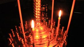 Dimly burning church candle on candlesticks stock video footage