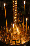 Dimly burning church candles. On candlesticks in church royalty free stock photography