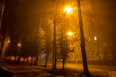 Dimly illuminated city street at night during a thick fog. Foggy evening royalty free stock photography