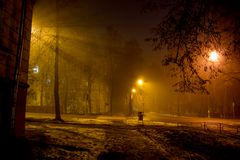Dimly illuminated city street at night during a thick fog. Foggy evening royalty free stock photo