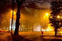 Dimly illuminated city street at night during a thick fog. Foggy evening stock photography