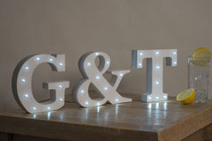 Dimly Illuminated Decorative Letters spelling Gin and Tonic G&T Royalty Free Stock Photos